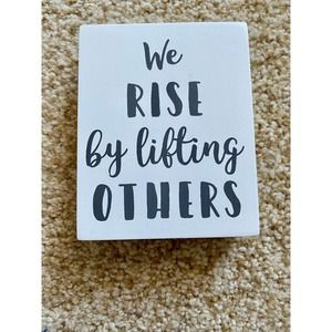 Young's Inc table sign We Rise by lifting others